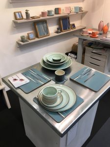 Table top with new Spiral Chun green plates in three sizes and large mug.