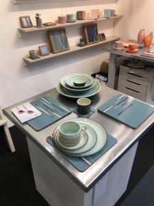 Table dressée avec les nouvelles assiettes vert chun dans une superposition de trois tailles surmontées d'un grand mug.